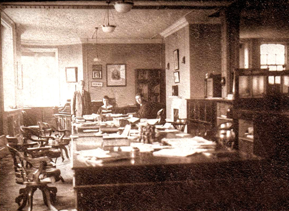 Photograph of office showing a long table surrounded by chairs with only three people around it